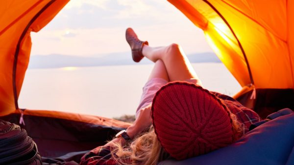 Woman lying in tent looking at view